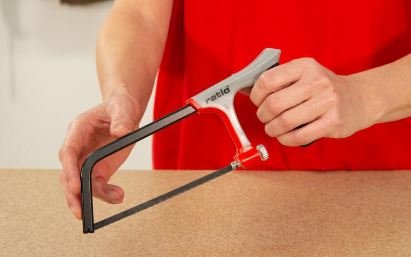 Corta los tubos de PVC con una sierra de arco