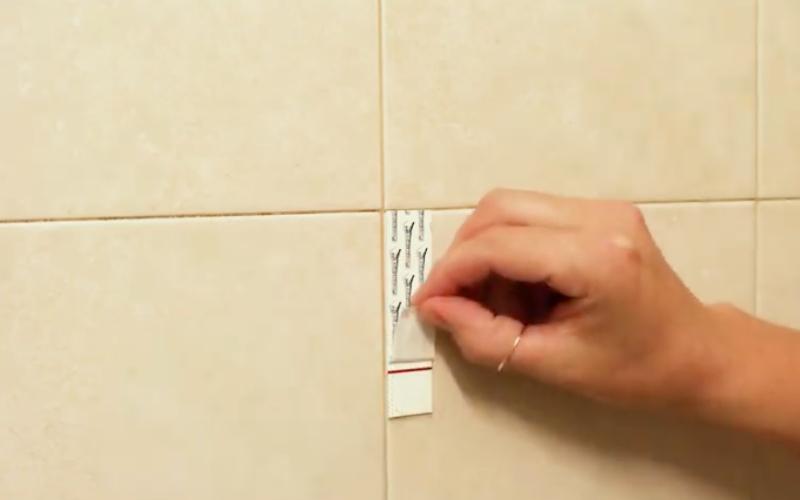 Pega la tira adhesiva en la pared o azulejo