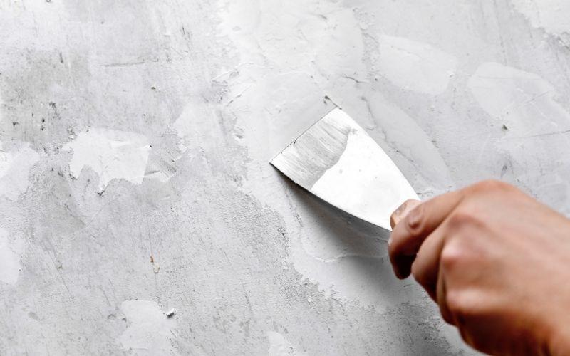 Extiende la masilla para tapar el agujero de la pared